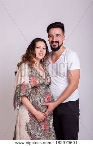 Pregnant smiling woman with her husband in studio photo. Wife and husband. Parenthood and expecting baby