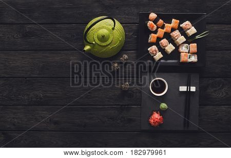 Japanese food restaurant top view with copy space, sushi and roll platter. Teapot and black slate plate with chopsticks on rustic wood background. Vintage filter