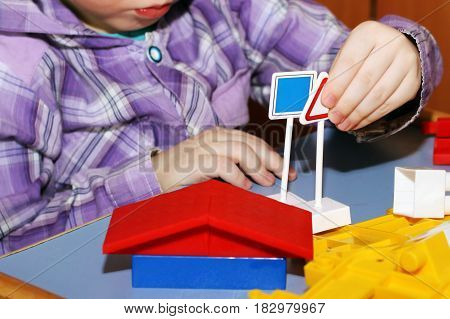 Child boy playing in color designer colored toy