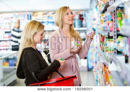 Young women shopping together in the supermarket with people in the background