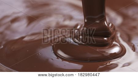 Slow motion of premium dark melted chocolate being poured from spoon in right part of frame, 4k photo