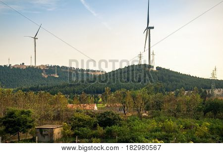 Tianjin, China - Nov 1, 2016: Image captured on High Speed Rail (HSR) from Tianjin to Shanghai, passing countryside with wind generators and other high-rise structures. Average speed: 300 km/h.
