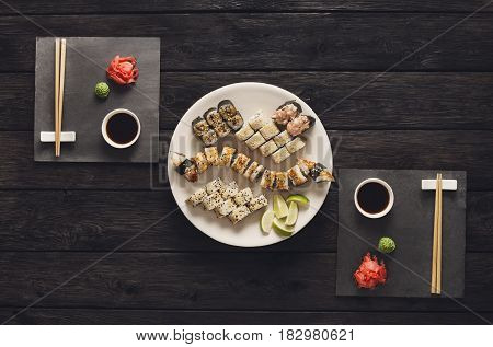 Japanese food restaurant, unagi roll sushi and maki platter. Set for two with chopsticks, ginger, soy, wasabi. Top view on rustic wood background and black slate plates.