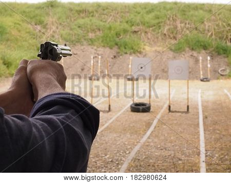 Gun with two hands, shot at shooting range.
