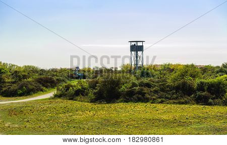 Backlit image of an observation tower in a Dutch dune area in the beginning of the spring season.