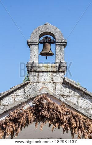 Old vintage brass bell on a ancient white stone chapel on a blue sky background