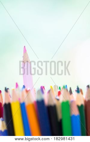 Pink wooden pencil stick out in stack of other color pen as unique innovation distinguish creativity hobby artistic colorful background