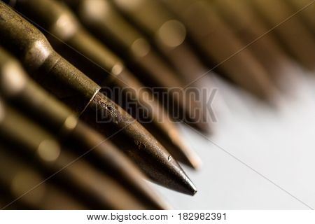 Closeup brass copper metal bullet lined up in a row as criminal crime violence danger killing death army danger sinister concept background