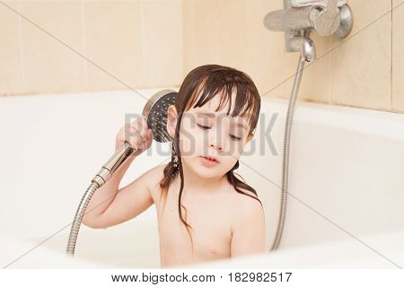 A girl (3-4 years old) sits in a bath and is washed with a shower head.