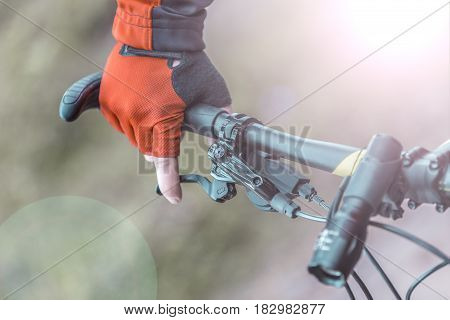 Biker holds breaks on handlebar of bike