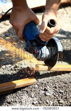 men's hands cut grinder metal pipe outdoor
