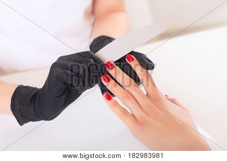 Hands in gloves cares about hands nails. Manicure beauty salon. Nails filing with file.