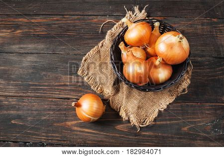 Raw golden onions in a basket on the wood table
