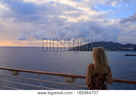 Blonde woman from back and view of St Maarten in Caribbean sea from cruise ship