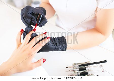 Hands in gloves cares about hands nails. Manicure beauty salon. Master paint nails with red lacquer.