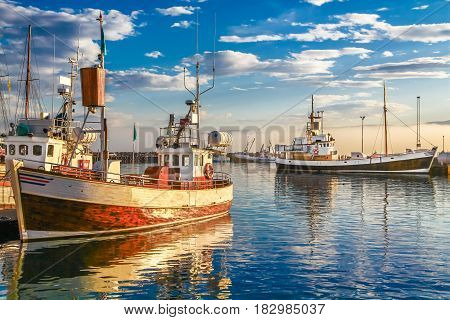 Panoramic view of traditional old wooden fisherman boats lying in harbor in beautiful golden evening light at sunset town of Husavik Skjalfandi Bay Iceland northern Europe
