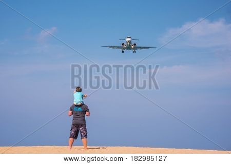 PHUKET THAILAND - MARCH 04 2017: Unidentified Father and children looking the plane was landing phuket international airport near Mai Khao Beach on Phuket Island in Thailand.