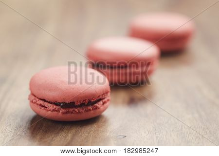 closeup shot pastel colored macarons with strawberry flavour on wood table, vintage toned photo