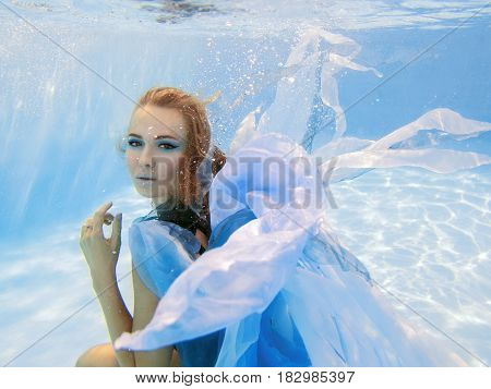 Underwater fashion portrait of beautiful young woman in blue dress
