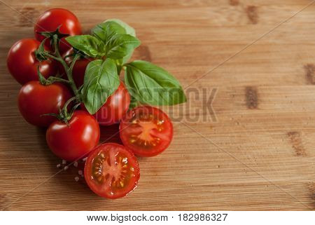 A twig of fresh red tomato with basil on a board with long ripening cheese