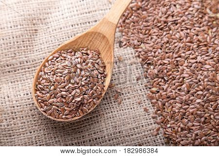 Flax seeds are scattered on a napkin of burlap