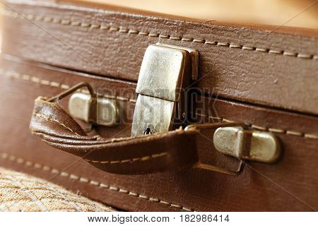 Old vintage suitcase in the room. The suitcase handle. Foreground horizontal photo