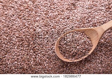Flax seeds are scattered a solid background in a pile of seeds wooden spoon with flax