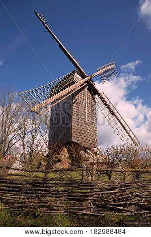 Old wooden fence and old windmill on a green field near wood
