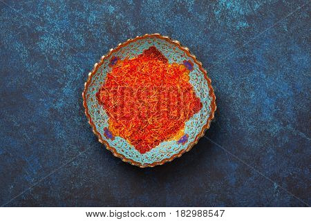 Saffron in a metal bowl on a blue background. View from above.