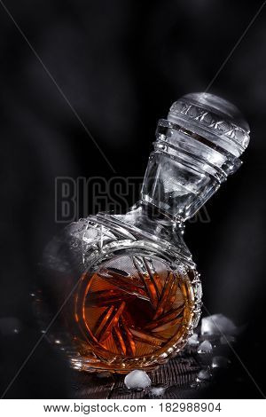 Crystal decanter full of strong alcoholic drink on a wooden table dark background
