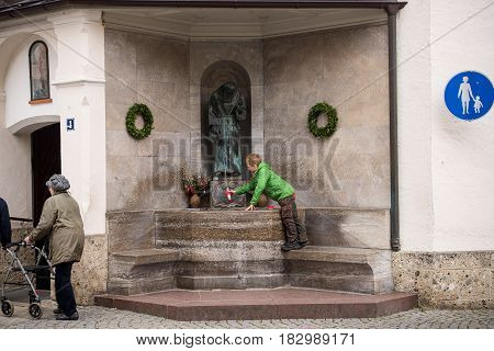 Altoetting,Germany-April 232017: A boy fills a bottle with holy water at a fountain outside a church