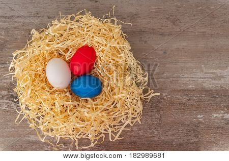 Easter tricolour eggs on a wooden background in the nest.