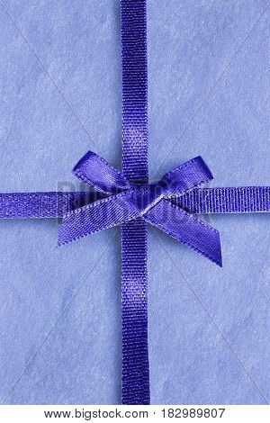 Blue silk decorative ribbon tied on blue paper closeup