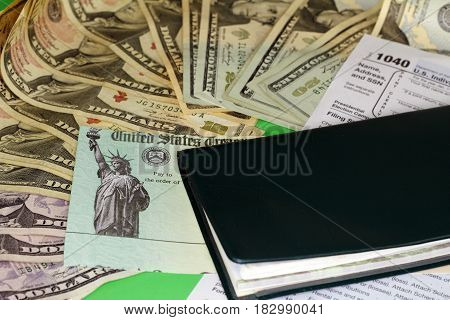 One checkbook on a 1040 tax form a tax refund check and a variety of cash paper money. A tax refund check with paper money a checkbook and a 1040 tax form.