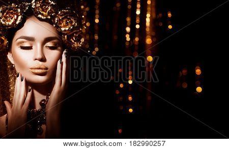 Gold Woman holiday makeup. Beauty fashion model girl with Golden make up, hair and jewellery on glowing background. Gold wreath and necklace. Fashion art portrait, Hairstyle, manicure and make up.