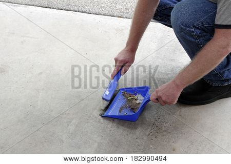 Male crouched down sweeping a cement garage floor of dust and debris with a small broom into a dustpan. Rubbish on a garage floor being swept into a dustbin by a man