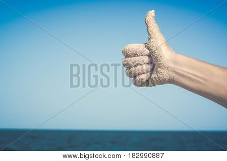 Woman's Hand Against Blue Sea