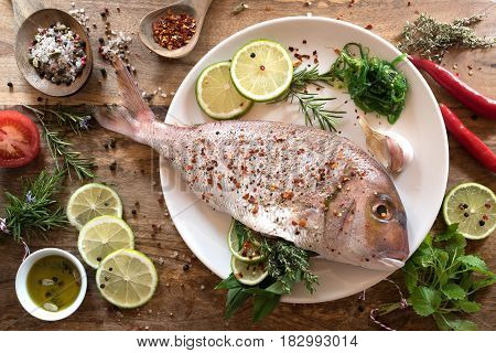 Dorade fish with herb filling and ingredients for grilling