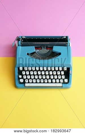 Vintage blue typewriter over a pastel background.