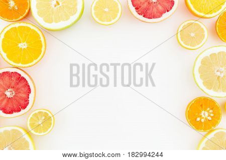 Food Frame of tropical summer mix with fresh lemon, orange, mandarin, grapefruit and sweetie on white background. Flat lay, top view.