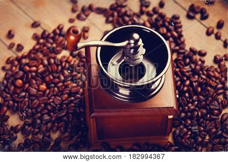 photo of coffee grinder and roasted beans on the wonderful brown wooden background
