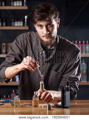 Man In A Vape Shop Is Filling A Special Liquid In E-cigarette.