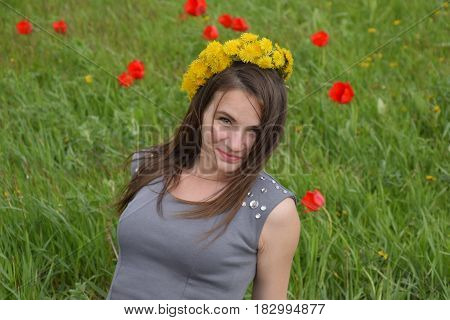 A Girl With A Wreath Of Dandelions On Her Head. Beautiful Fairy Young Girl In A Field Among The Flow