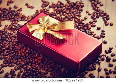 photo of beautiful cute gift and roasted coffee beans on the wonderful brown wooden background