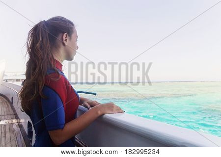 Young Adult Woman In A Wet Suit Looking Out Into The Distance At Sea