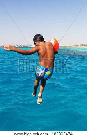 Little arabic boy jumping into the blue water of the sea with yachts.