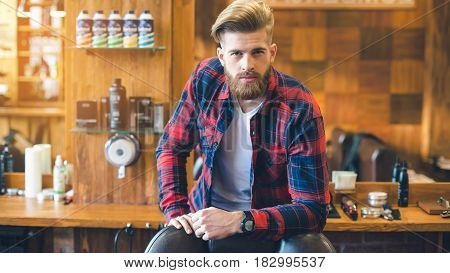Young man in a barbershop confident look done with hairstyle