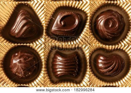 Chocolate Candies Of Different Shapes In A Gold Box, Top View, Smooth Symmetrical Rows For Backgroun