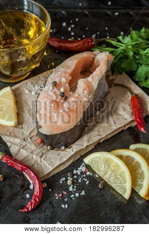 Raw Fresh Steak Trout Fish On Paper, Around Greens, Leaves, Lettuce, Lemon, Olive Oil, Pepper, Chili