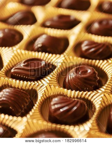 Chocolate Candies Of Different Shapes In A Gold Box, A Perspective View And Blur
